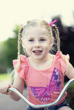 Happy little girl on bike Royalty Free Stock Photography