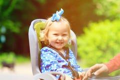 Happy little girl on bike seat Stock Photography