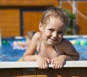Happy little Girl in bikini swimming pool stock images