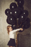 Happy little girl with black balloons. Stock photo. Stock Image