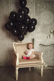 Happy little girl with black balloons. Stock photo. Royalty Free Stock Photos