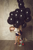 Happy little girl with black balloons. Stock photo. Royalty Free Stock Images