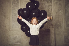 Happy little girl with black balloons. Stock Photos