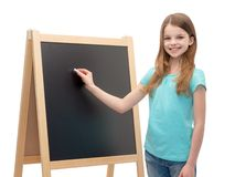 Happy little girl with blackboard and chalk Stock Images
