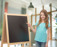 Happy little girl with blackboard and chalk Royalty Free Stock Images