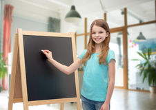 Happy little girl with blackboard and chalk. People, children, advertisement and education concept - happy little girl with blackboard and chalk over school Royalty Free Stock Image
