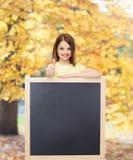 Happy little girl with blank blackboard Royalty Free Stock Image