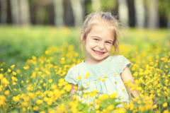 Happy little girl on blooming meadow Stock Photography