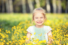 Happy little girl on blooming meadow Royalty Free Stock Image