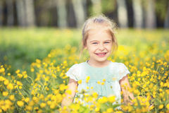Happy little girl on blooming meadow Stock Image