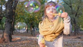 Happy little girl blow air bubbles and smiling in park on background trees. Happy little girl blow air bubbles and smiling in autumn park on background trees stock footage