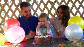 Happy little girl blowing out candle on her birthday cake and her loving parents kiss the her and clap the hands stock footage