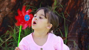 Happy little girl blowing on a pinwheel. In the countryside stock video footage