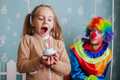 Happy little girl blows out the candle on cake. Birthday party concept Stock Photography