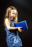 Happy little girl with blue book in her hands Royalty Free Stock Photos