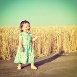 Happy little girl in blue dress Stock Photos