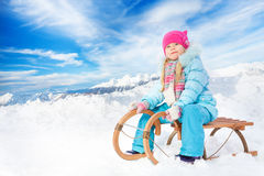 Happy little girl in blue on sledge Royalty Free Stock Images