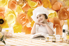 Happy little girl with book chef preparing Breakfast in the kitchen Royalty Free Stock Image