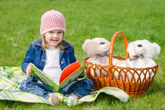 Happy little girl with a book on a picnic Royalty Free Stock Photos