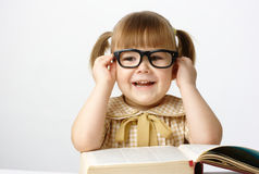 Happy little girl with books wearing black glasses Stock Photos