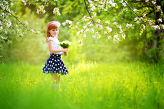Happy little girl with a bouquet of lilies of the valley having Royalty Free Stock Photography
