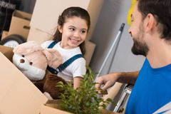 Happy little girl with box of plush toys looks at father which started repair in house. royalty free stock photos