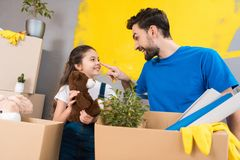 Happy little girl with box of plush toys looks at father which started repair in house. royalty free stock images