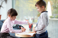 Happy little girl and boy drawing at home. Childhood, leisure, friendship and people concept - happy little girl and boy drawing and coloring picture with Stock Photo
