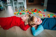 Happy little girl and boy enjoy play home. With toys scattered around royalty free stock photos