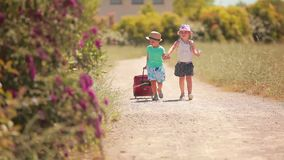 Happy little girl and boy holding hands, go on the road. With a suitcase stock video footage