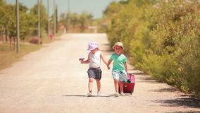 Happy little girl and boy holding hands, go on the road. With a suitcase stock footage