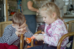 Happy little girl and boy playing with a doll Stock Image