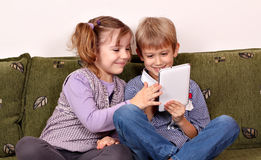 Happy little girl and boy playing with tablet Stock Photos
