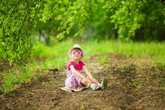 Happy little girl in bright dress and funny sunglasses walk in summer garden. Happy little girl in bright dress and funny sunglasses walk in garden royalty free stock photo
