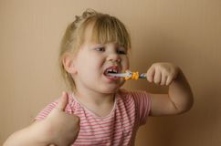 Happy little European girl brushing her teeth royalty free stock photography