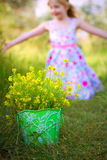 Happy little girl and a bucket of flowers in the park Stock Photos