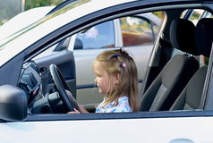 Happy little girl in the car. Happy little child, funny blonde toddler girl sitting on her knees inside of the car on driver seat holding steering wheel Royalty Free Stock Image
