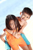 Happy little girl carrying her brother Royalty Free Stock Photo