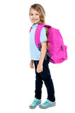 Happy little girl carrying school bag Stock Photos