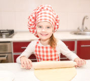 Happy little girl with chef hat rolling dough Royalty Free Stock Images
