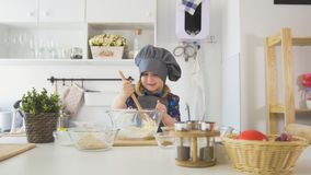 Happy little girl chef mixing the dough with big wooden spoon in glass bowl. Horizontal Royalty Free Stock Photography
