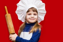 Happy little girl in chef uniform holds rolling pin isolated on light background. Kid chef. Cooking Process Concept stock photography