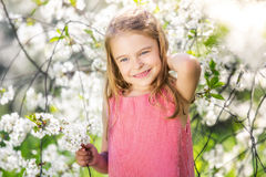 Happy little girl in cherry blossom garden Royalty Free Stock Photography