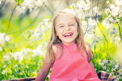 Happy little girl in cherry blossom garden. Happy little girl playing in spring cherry garden Royalty Free Stock Photography