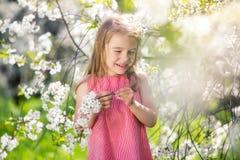 Happy little girl in cherry blossom garden Stock Photo