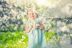 Happy little girl in cherry blossom garden Stock Images