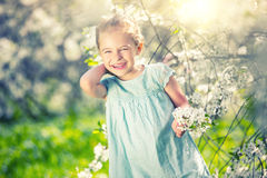 Happy little girl in cherry blossom garden. Happy little girl playing in spring cherry garden Stock Photography