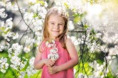 Happy little girl in cherry blossom garden. Happy little girl playing in spring cherry garden Royalty Free Stock Image