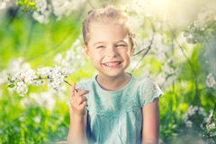 Happy little girl in cherry blossom garden Stock Photography