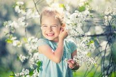 Happy little girl in cherry blossom garden. Happy little girl playing in spring cherry garden Stock Photo